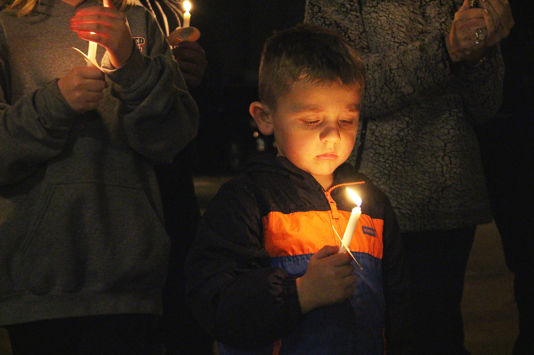A candlelight vigil was held during a bench dedication in honor of James F. Creason at Friday's Christmas Caroling Event in Bowman, and the candle shines here on Creason's great-grandson, Easton Moss. (Photo by Scoggins)