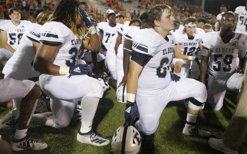 Blue Devils (L-R) Tamar Burton, Seth Capps and A.J. German take a knee to listen to head coach Brad Waggoner after losing to Hart County Friday night Aug. 23 in Hartwell. (Photo by Cary Best)