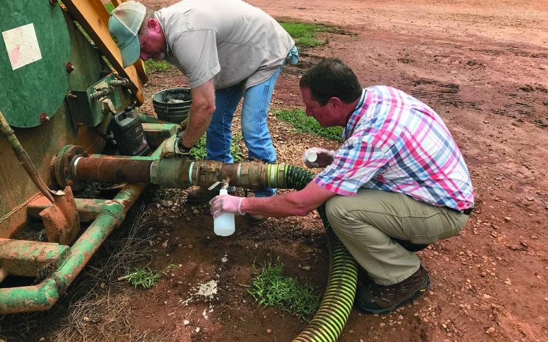 Patrick Marcellino (right) of the University of Georgia's Elbert County Extension Service and Chad Duffell (left) of Broad River Valley Farms draw fluid from a holding tank in a file photo from 2018 at the River Road facility.  (Photo by Jones)