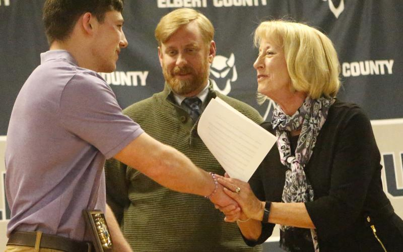 Senior Gavin Brady (left) accepts the Kyle D. Wilhite Memorial Wrestling Award from Clint Wilhite and Connie Spivey during the Elbert County High School 2019-2020 Winter Sports Athletic Program March 9 in the middle school auditorium. (Photo by Cary Best)