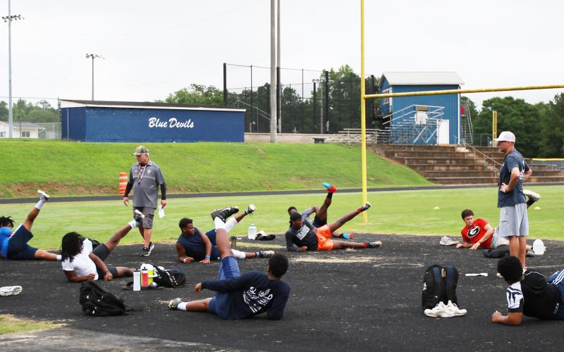 Elbert County football coaches Tommy Gilstrap (left) and Reuben Haynes (right) work with Blue Devil football players during voluntary player workouts Monday morning. Two groups of players worked out on Monday morning under guidelines issued by the state and the Center for Disease Control. (Photo by Scoggins)