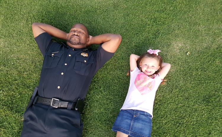 aking it easy is Elberton Police Capt. Darin Rucker (left) and a friend, Aspen Wright, who are relaxing after an event Rucker conducted as a part of the Elberton Police Department's relationship-building efforts in the community.