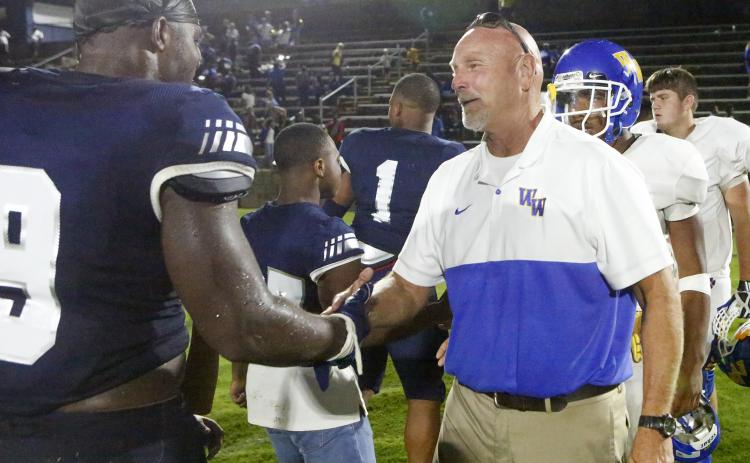 Washington-Wilkes offensive line coach and former Elbert County head coach Sid Fritts (right) shakes hands with senior Blue Devil Qwen Moss after Friday night's game Aug. 30 in Elberton. (Photo by Cary Best)