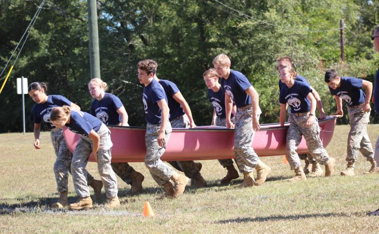 Elbert County JROTC Mix Team members (L-R) Marilyn Flores, Makayla Ingle, Haylee Marunich, Mathew Fernandez, Dean Blanchard, Justin Bastyr, Brandon Nestor, Maelynn Ruff, Gabriel Ruff and Thomas Vaughn race through the physical team test event while holding a canoe during a home Raider meet Oct. 12. (Photo special to The Star).
