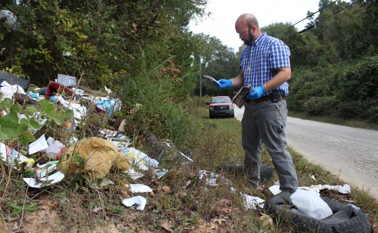 Investigation in progress – Allen Hulme looks for clues after he finds dumping in a remote area of Elbert County. (Photo by Scoggins)