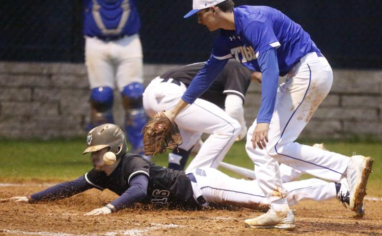 Blue Devil senior Brayden Eavenson scores as Tiger Nathan Durham (right) attempts to make a tag in the fifth inning of Elbert County's 9-0 home-opening win over Washington-Wilkes Feb. 10 on Devils Field. (Photo by Cary Best)