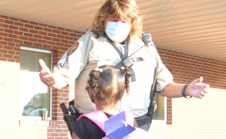 Elbert County School Resource Officer Tammy Gilliard welcomes a student on the first day of school at Elbert County Primary School Monday. (Photo by Jones)