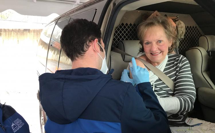 Kathy Pfaender of Hartwell gets a vaccine from Athens Tech nursing student Alex Higgins at EMH's drive-through Monday morning. (Photo by Jones)